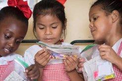 three children holding school supplies in a plastic
